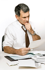 Confused Man Reading a Bill or Bank Statement