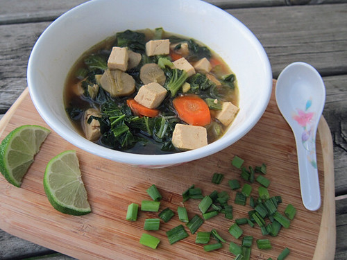 A big bowl of soup sitting on a wooden board. In the bowl you can see carrots, burdock roots, cooked greens, and cubed tofu. To the right of the bowl is a pho spoon. In front of the bowl are sliced green onions and a few slices of lime.
