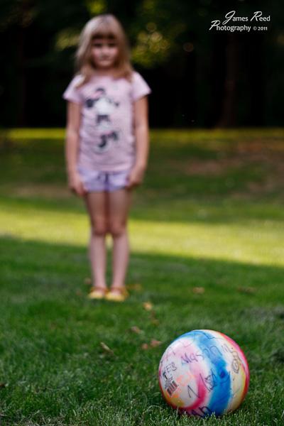 The little one eyes her kickball.