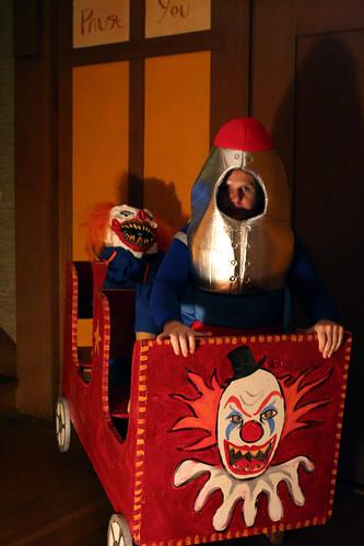 A clown behind Mo in a carnival ride car