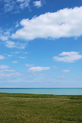 puffy clouds in sky over lake that is two blues and green grass shore