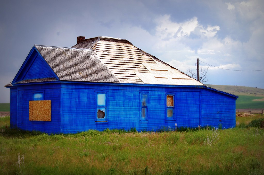 abandoned house painted bright blue in the middle of nowhere