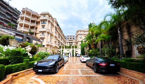 An alleyway littered with Porsches and Maseratis.