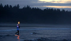 Surfer Ruth Sadler, 72, carries the Olympic Flame into the Pacific Ocean for a torch exchange, Vancouver 2010 Winter Olympic Games, Pacific Rim National Park, Canada, by Darryl Dyck