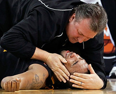West Virginia's Da'Sean Butler is consoled by head coach Bob Huggins after injuring his knee,  NCAA college basketball semifinal, Indianapolis, 2010, by Mark Blinch