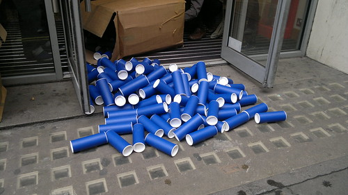 """Picture showing an open doorway, onto a street, through which a large number of blue cardboard poster tubes have spilled from a cardboard box that someone clearly struggled to get through the door with, captioned """"oops""""."""