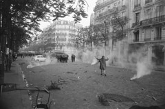 Near the intersection Mabillon, in a cloud of tear gas, this young woman defies the CRS, Paris, 1968, by Goksin Sipahioglu