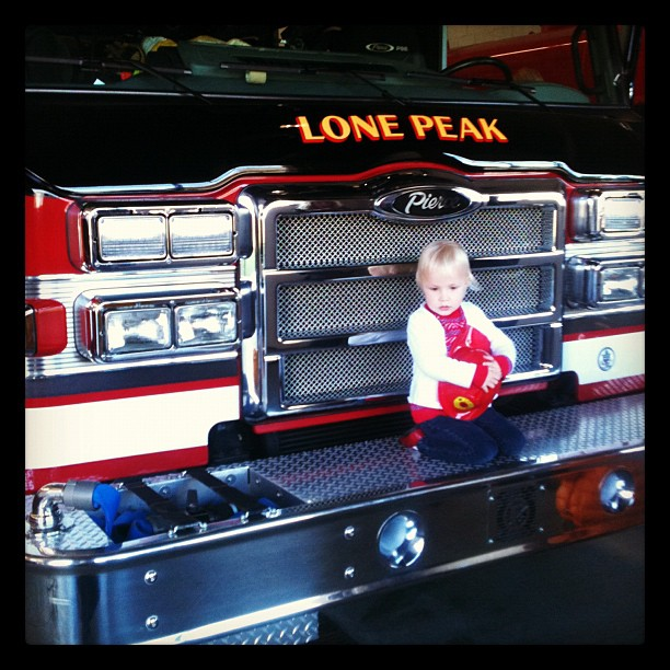Visiting the fire station. She is so tiny on that truck!
