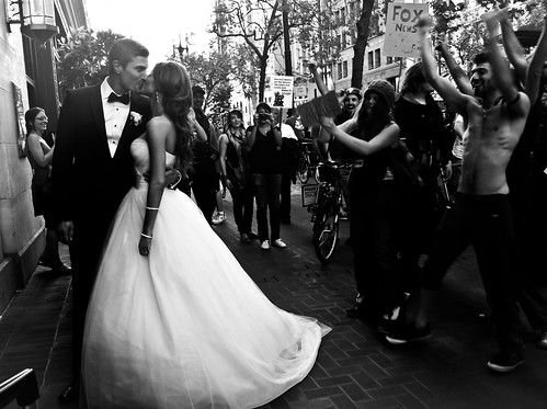 Photo of a couple kissing as Occupy SF marches by