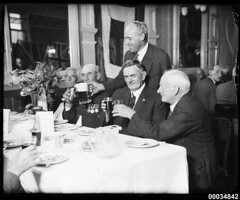 Retired military personnel at a table drinking...