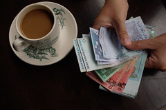 A customer counts Malaysian ringgit at a cafe ...
