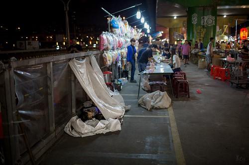 三重新光市集-小窩,夜市擺攤兼帶小孩,只好在一旁用簡易的布幕搭出小空間,在這吵雜的夜市裡有個小天地陪陪孩子玩耍,照片中媽媽正陪小孩窩在小天地裡。