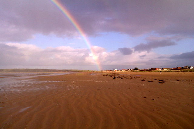 Photo of a rainbow over the beach