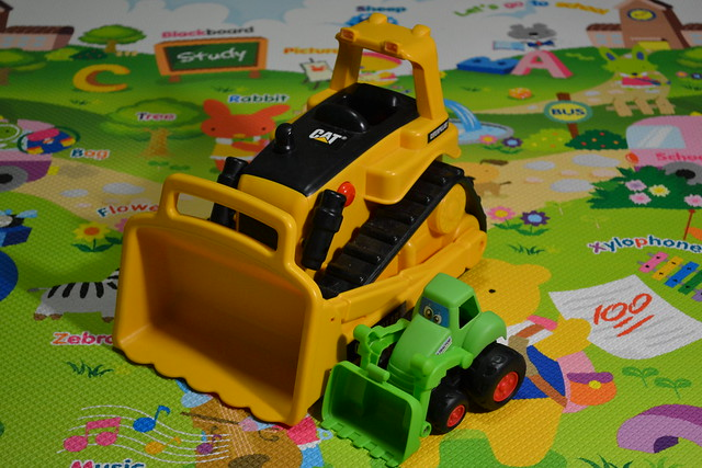 A photo of two related objects of drastically different sizes - Toy trucks