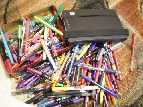 A pile of pens of various colors with a moleskin journal tossed on top