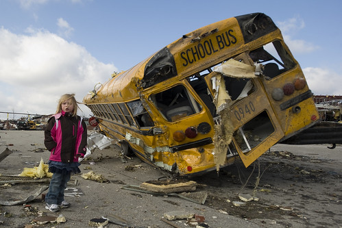 Image of girl standing next to destroyed school bus.