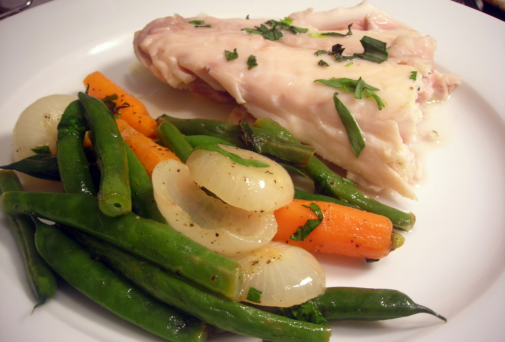 Poached wild striped bass, tarragon butter sauce and spring vegetables