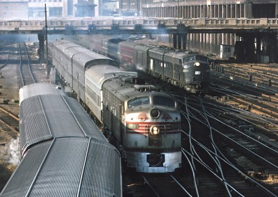 BN 9937 (E8A, ex-CB&Q 9937) with a Dinkey and PC 4305 (E8A, ex-PRR 5905) with the Broadway Limited on March 30, 1971 south of Chicago Union Station