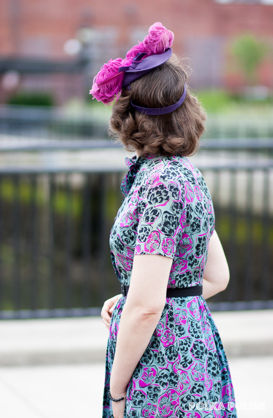 Abstract floral 1940s dress in pink, black, and blue paired with a New York Creation tilt hat in purple with pink ostrich feathers