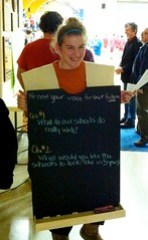 A student wears a sandwich board asking community members questions about the future of their schools.
