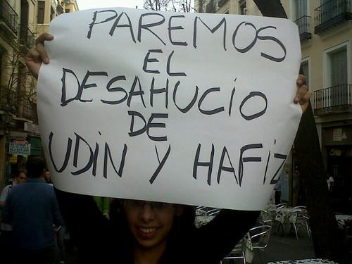 """Una vecina muestra un cartel """"Paremos el desahucio de Uddin y Hafiz"""""""