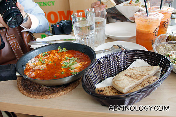 The Red Shakshuka in a pan and a piece of plain pita