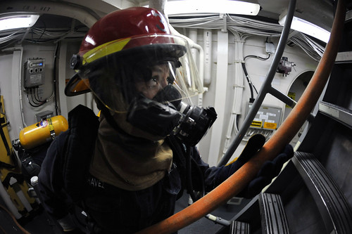 A Sailor passes a fire hose to Sailors fighting a simulated fire during a damage control drill. by Official U.S. Navy Imagery