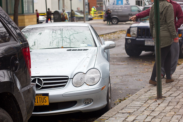 A Mercedes Benz that got submerged in flood water, then dragged away from the curb.