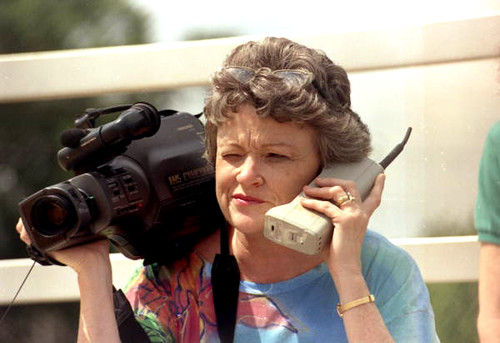 Journalist Lucy Morgan with video camera and phone by State Library and Archives of Florida