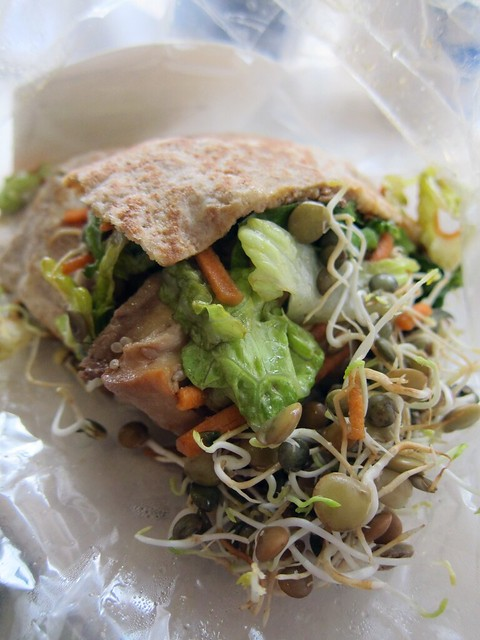 A pita stuffed with tofu, veggies, and sprouts.