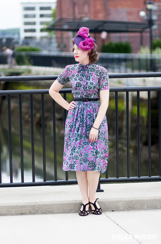 1940s daytime look featuring a dress with an abstract print of black, aqua, and hot pink and a tilt hat with a towering pile of feathers.