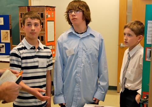 Three students present a history project on World War II.
