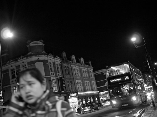 A woman talks on the telephone while a bus passes behind her