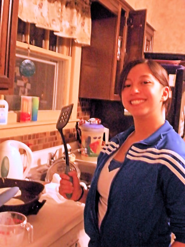 She smiles holding up a spatula while tending an electric skillet of  pancakes