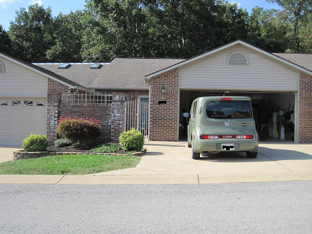 Front of the condo with their new Nissan Cube parked in the driveway