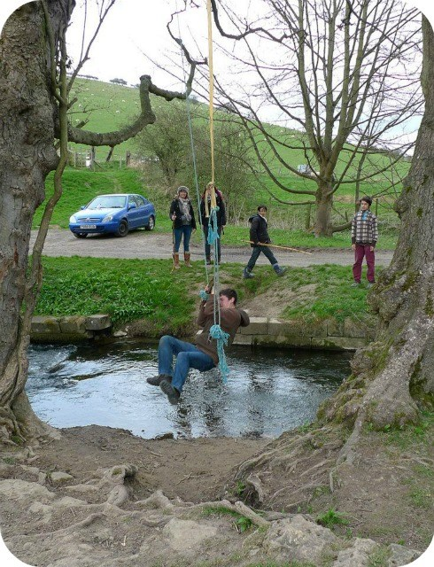 Man on a rope swing over a stream