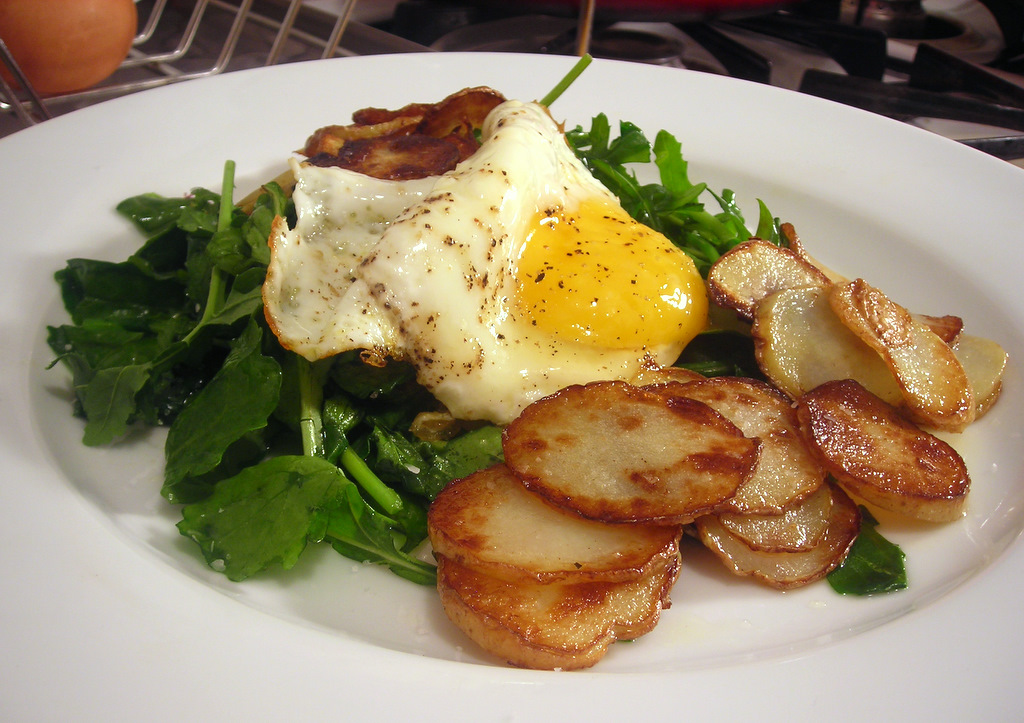 Arugula and Bordeaux spinach salad, with fried farm egg and homemade sea salt and sherry vinegar potato chips
