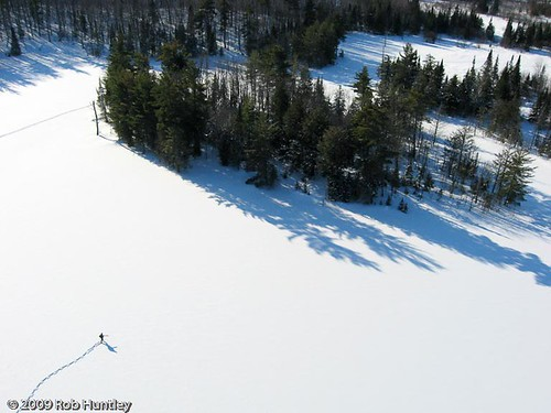 Hiking across Fortune Lake.  Fortune Lake in Gatineau Park, Quebec with a lone hiker on snowshoes. Actually it is yours truly carrying an extra kite (looking like a rifle). Kite line has been erased.