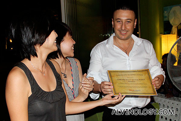 Qiuyan and Angeline from SOLD.sg presenting a certificate of appreciation to the boss man at Limoncello
