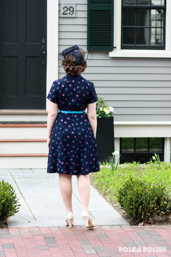 A 1940s daytime look in navy, teal, and pink with a small tilt hat and cream BAIT Footwear heels