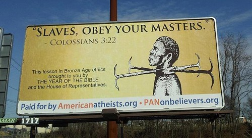 billboard depicting an illustration of a shackled black man. Text reads: Slaves, obey your masters. This lesson in the Bronze Age brought to you by the year of the bible and the house of representatives.