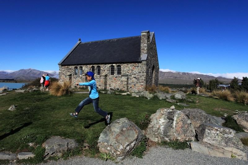 小男孩跳躍在紐西蘭好牧羊人教堂前