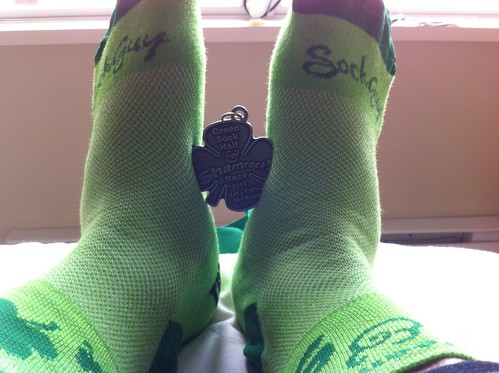 A pair of green socks that were provided to participants of the Green Sock Half Marathon, along with the finisher's medal.