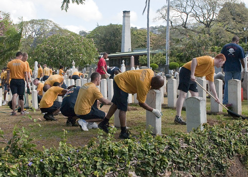 Sailors clean plots of fallen service members at an Oahu cemetery during a community relations project. by Official U.S. Navy Imagery