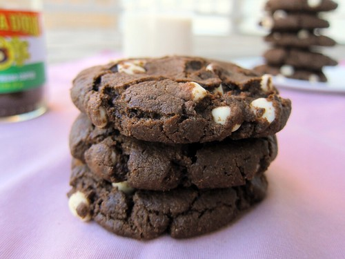 In the foreground, three chocolate cookies with white chocolate chips. In the background, a container of instant espresso powder, a glass of soymilk, and a stack of more cookies.