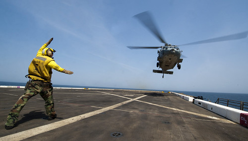 A Sailor signals a helicopter to land on the deck. by Official U.S. Navy Imagery