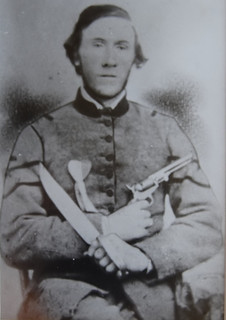 posing in Confederate uniform with saber and gun.  There is a heart shaped medal on his chest.
