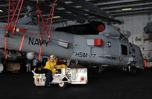 A Sailor moves a helicopter in the hangar bay. by Official U.S. Navy Imagery