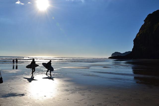 Surfers at Piha Beach