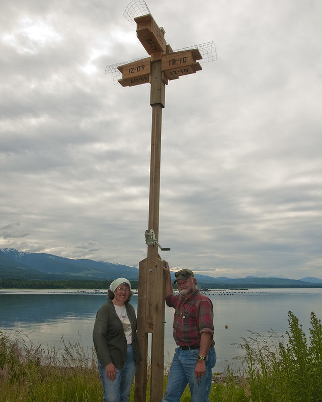 Charlene Lee and Bruce Cousens pose with the newly installed purple martin nest boxes.